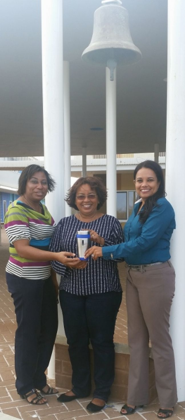 Deputy Director Charlotte Dortalina (left) and Director Patricia Angela (right) from Skol Amplio Papa Cornes on Bonaire, are receiving a tumbler from senior Policy Advisor Maritsa Silberie of RCN/OCW. (Photo contributed)