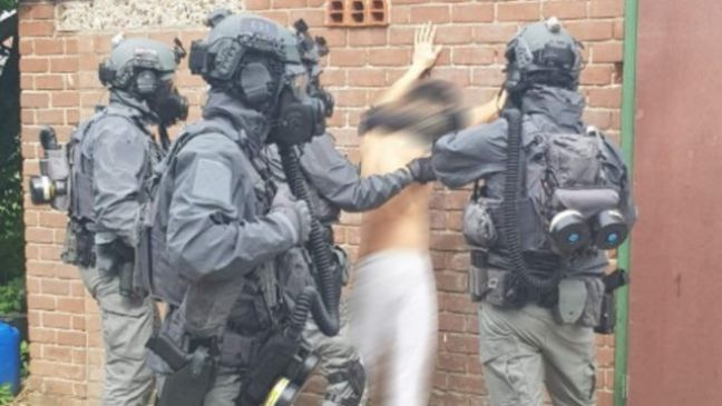 Police in protective gear making an arrest at the farmhouse. Photo: Politie.nl