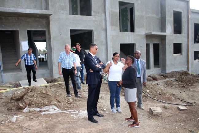 Minister stands outside the Town Houses and speaks to Contractors and APS representatives about the project.