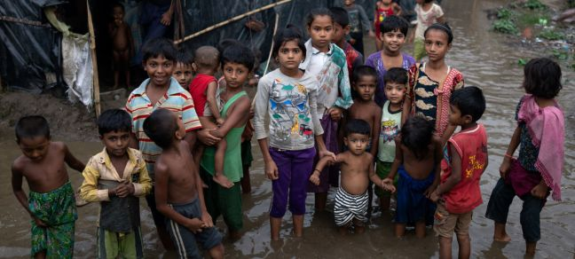 UNICEF/UN0213967/Sokol Pictured here, Rohingya refugee children wade through flood waters surrounding their families' shelters following an intense pre-monsoon storm in Shamlapur makeshift settlemen in Cox's Bazar district, Bangladesh.