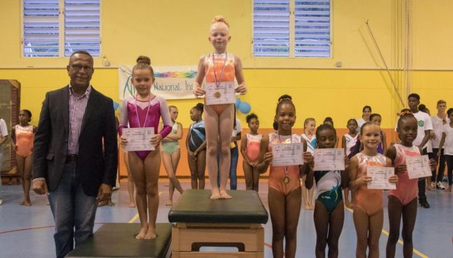 Minister of Education, Culture, Youth & Sports Wycliffe Smith (left) with gymnasts.