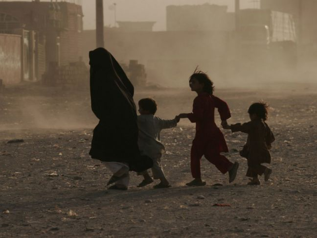 UNAMA/Fraidoon Poya A woman along with her children runs across a dusty street in Herat, western Afghanistan. Civilians across the country continue to bear the brunt of the conflict.