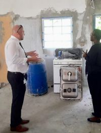 In the photo on the left is Acting Minister of VSA Christopher Wever inspecting one of the homes being repaired.