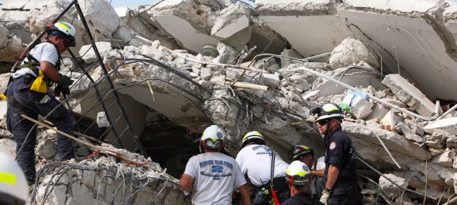 UN Photo/Sophia Paris Rescuers search through a United Nations building destroyed by the earthquake which struck Haiti on 12 January, 2010.