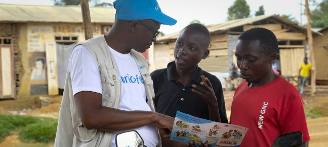 © UNICEF/Thomas Nybo On 12 September 2018 in Beni, a UNICEF staff member discusses the best way to protect yourself against Ebola in a conversation with young people living in Beni, Democratic Republic of Congo, after a recent Ebola outbreak.