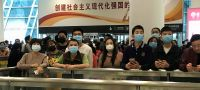 UN News/Jing Zhang People wear face masks as they wait at China's Shenzhen Bao'an International Airport arrivals.