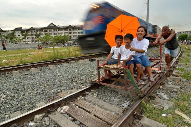 A train passing a 'trolley' - a makeshift rail cart made with wood or bamboo - in Manila, the Philippines. Photo: ESCAP/Anthony Into