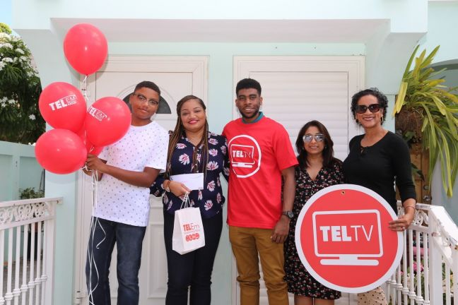 TelTV prize-winner, Marinka Gumbs, (2nd left) and son Christopher, (left) were happy with a personal visit from TelTV representatives, Naeem Dupersoy (center) and Cheryl Rismay (right), along with ticket sponsor, Kisha Khemchandani of KK Travel (2nd right).