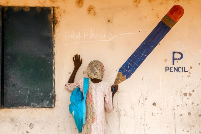 Aisha pretends to draw at the tip of a pencil painted on a wall mural in a camp for internally displaced people in Yola, the capital of Adamawa. Photo: UNICEF/NYHQ2015-0477/Esiebo