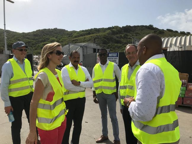 Mr. Jeffrey Lewis of Statia Waste Management Plant informs State Secretary Stientje van Veldhoven about waste separation and recycling process. Government Commissioner Marcolino Franco and Deputy Government Commissioner Mervyn Stegers look on.
